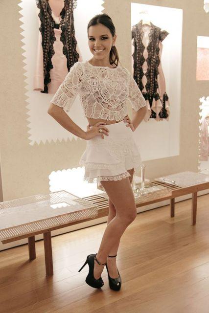 Mariana Rios usa blusa cropped de renda branca, saia curta branca e sapato preto.