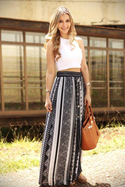 Modelo veste saia estampa em preto e cinza com cropped branco e bolsa cor terra.