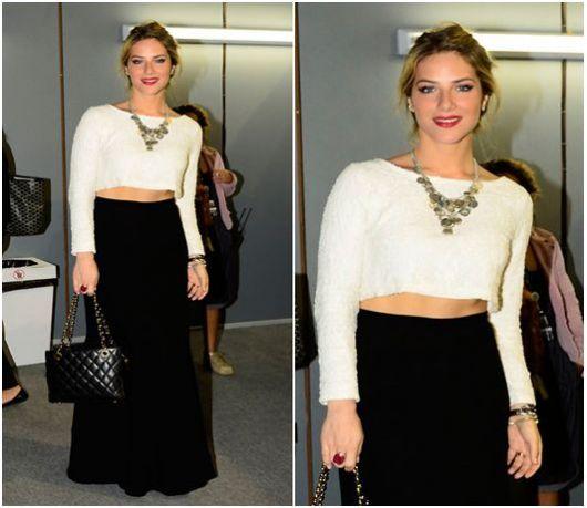 Giovanna Ewbanck usa saia preta lisa modelo longo com cropped manga longa branco, bolsa preta e colar em tom prata.