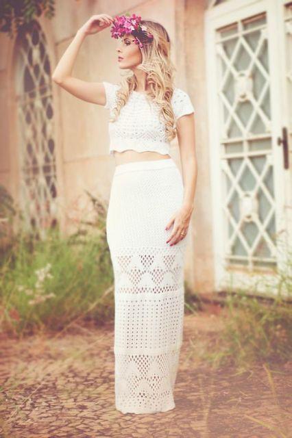 Modelo usa saia branca de croche, com blusa cropped de croche, modelo de manguinhas.