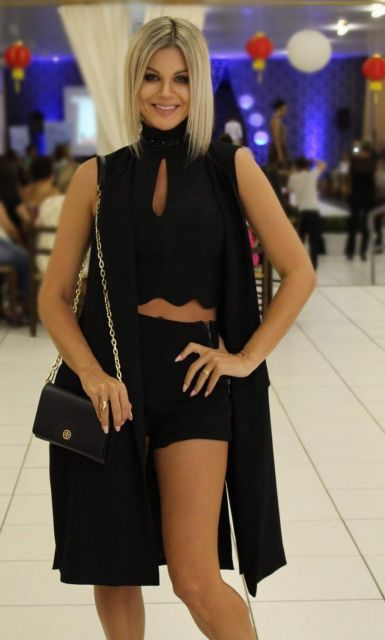 modelo veste cropped preto, short, bolsa e maxicolete na mesma cor.
