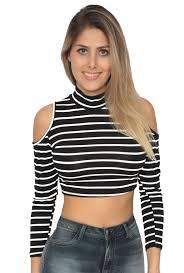 modelo veste blusa preto e branco com ombros vazados, jeans e cabelos soltos.
