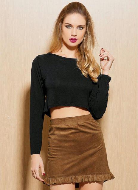 modelo usa cropped preto simples, saia marrom e cabelos soltos.