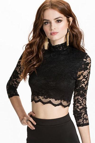 modelo usa cropped preto meia manga com brincos grandes de ouro.