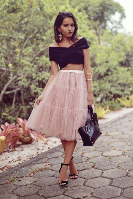 modelo usa saia midi rosê, sandalia de salto, cropped, bolsa e blusa preta.