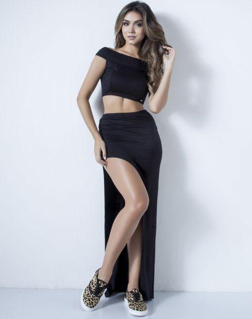 modelo usa saia preta, blusa cropped preta e tenis estampa de onça.