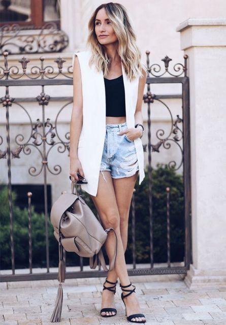 modelo usa maxi colete branco, short jeans, cropped preto e mochila cor nude.