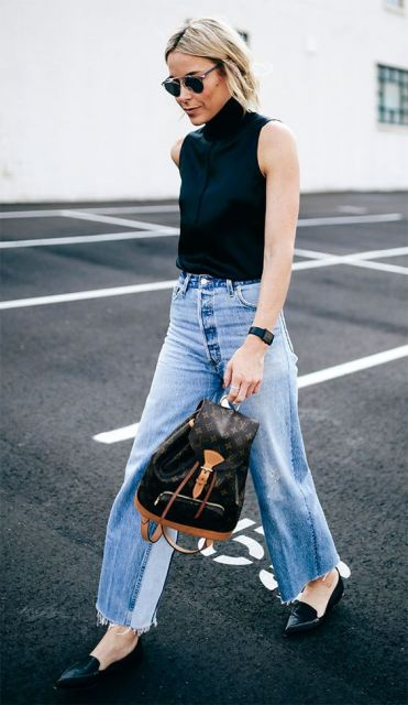 modelo usa calça jeans clara, cropped preto e sapatilha preta.