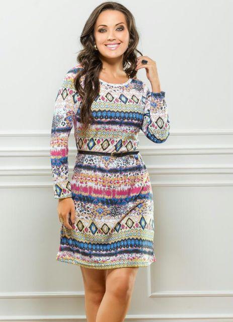 modelo usa vestido manga longa com estampa etnica azul, rosa, verde em fundo cinza.