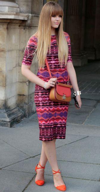 modelo usa sapato laranja, vestido etnico vermelho e bolsa nas cores de vermelho e marrom.