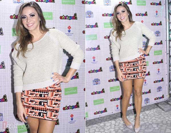 modelo saia estampada na cor laranja e preto, blusa branca sapato no mesmo tom.