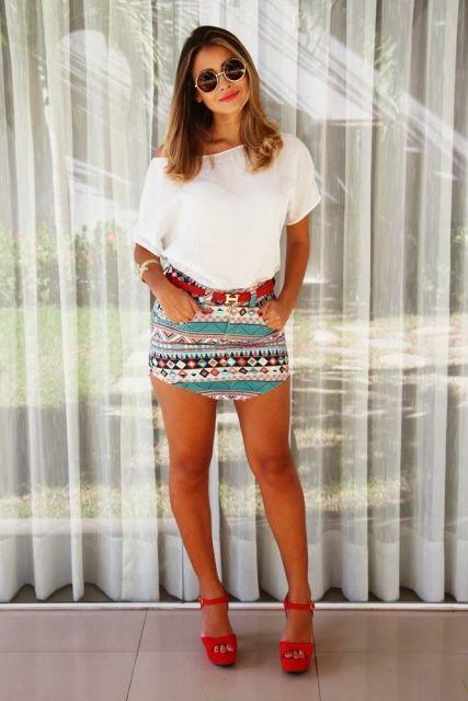 modelo veste saoa estampada etnica, com blusa branca, cinto vermelho e sapato no mesmo tom.