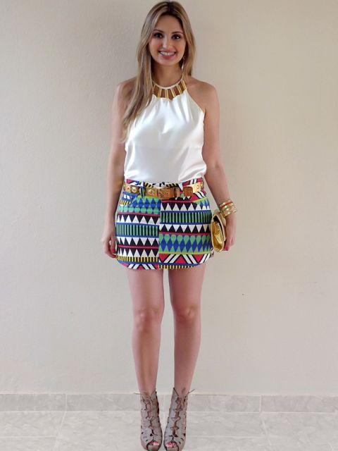 modelo veste saia azul estampa etnica, blusa branca, sandalia de amarração tom nude.