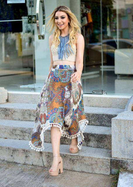 modelo veste saia tamanho médio, blusa nude e sapato no mesmo tom, com colar azul.