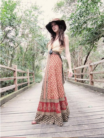 modelo veste saia longa estampada, blusa cor gelo e chapéu.