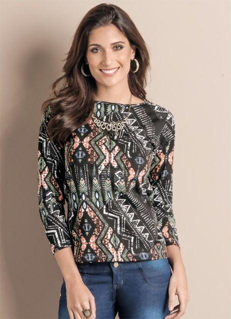 modelo veste blusa em tons fechados, com estampa étnica e calça jeans.