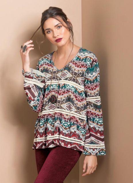 Modelo veste blusa estampa étnica manga longa com calça em tons bordô.