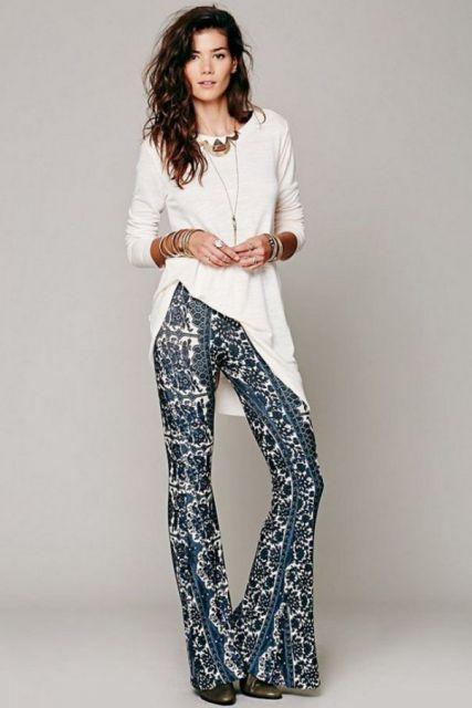 Modelo veste calça estampa etnica azul com branco e blusa meia manga na cor branca.