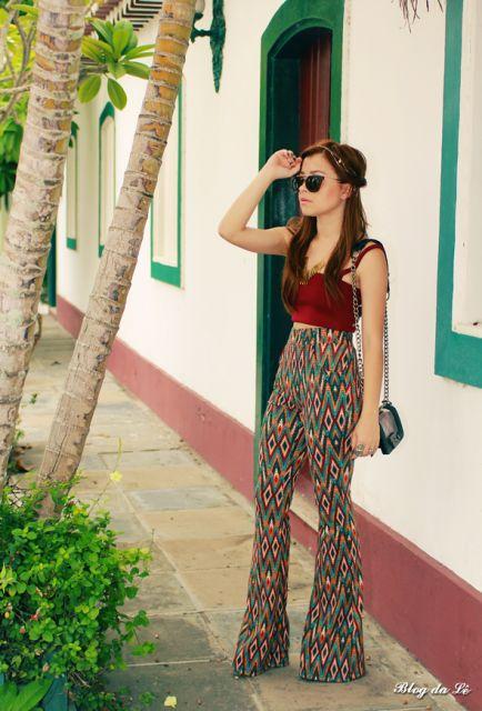 modelo veste calça flare, com blusa cropped vermelha de alcinha.