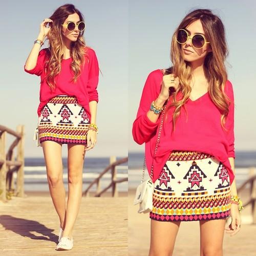 modelo usa saia estampa etnica, blusa vermelho rosado, bolsa e tenis branco.