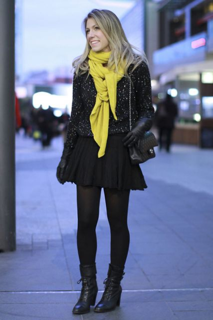 modelo veste saia, meia, blusa, casaco e bota preta com lenço amarelo.
