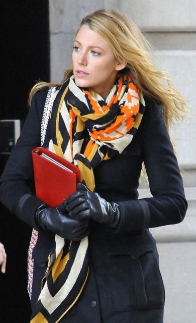 Blake lively usa lenço estampado em amarelo, branco, laranja e preto, com blazer preto e luvas de coro, no mesmo tom.
