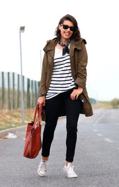 modelo usa blusa listrada preta e branca, calça preta, tenis e casaco.