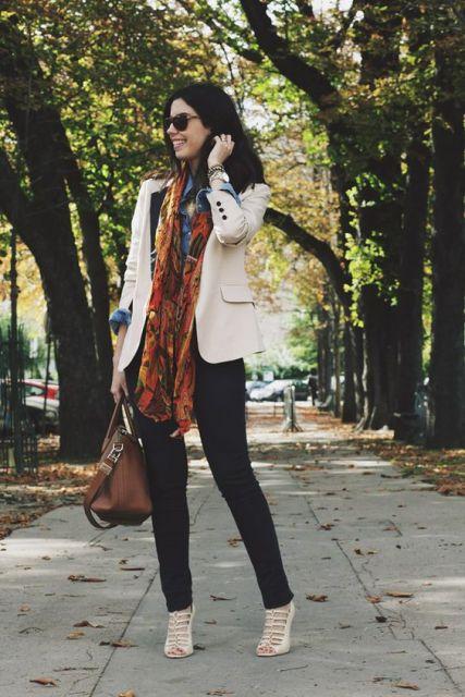 Camila Coutinho usa calça preta, blazer e sapato nude e bolsa e lenço marrom.