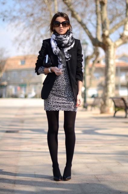 Modelo usa vestido cinza estampa discreta, blazer, lenço em preto e branco.