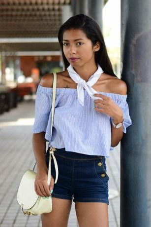 modelo usa blusa azul ombro a ombro, short e bolsa branca e lenço na mesma cor.