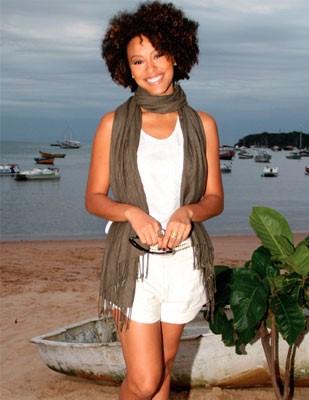 Sharon Menezes usa short e blusa branca, echarpe lenço verde musgo.