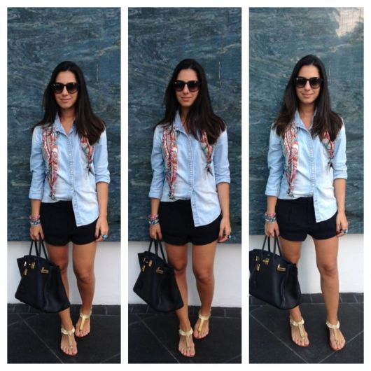 modelo usa short preto, camisa jeans azul e chinelo dourado.