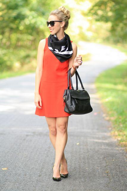 modelo veste vestido laranja, sapato preto e lenço nas cores preto e branco, com bolsa na mesma cor.