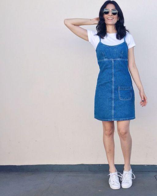 Modelo usa salopete azul clara com tenis branco e blusa branca.