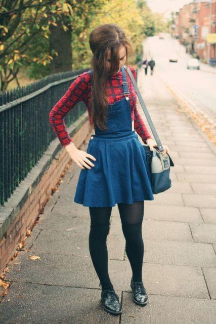Modelo usa vestido godê salopete com blusa vermelha estampa xadrez e sapato preto com bolsa.