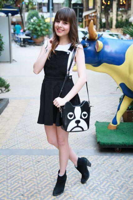 Modelo usa salopete preta, blusa branca, botinha preta e bolsa preto e branco.