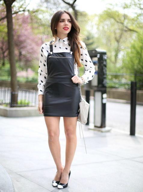 Modelo usa sapato preto e branco fechado, camisa branca com bolinha preta e salopete preta modelo reto.
