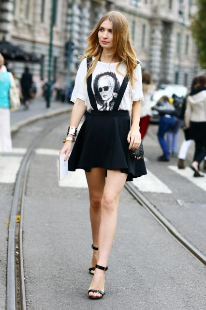 Modelo usa blusa branca estampada, salopete preta com suspensório e sandália preta, tiras finas.