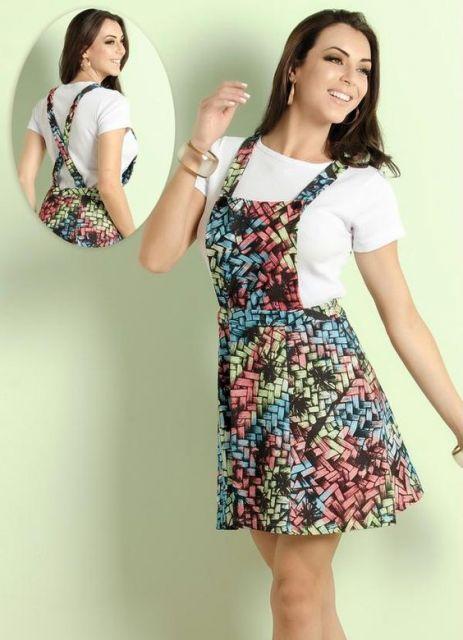 Look com salopete colorida em tons de azul, rosa e verde com blusa branca.