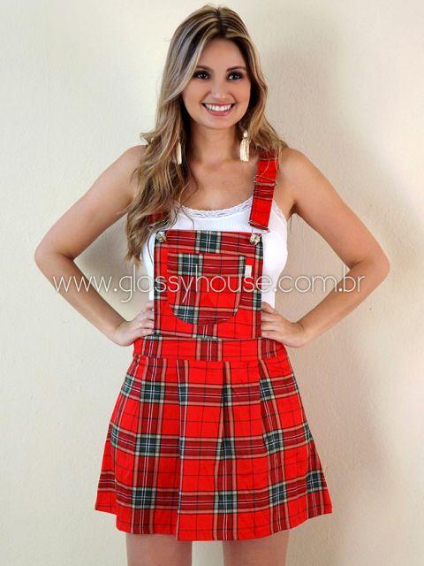 Modelo usa salopete vermelha com estampa xadrez e blusinha de alças branca.