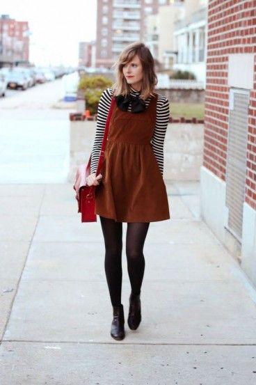 Modelo usa salopete marrom, meia transparente, sapatinho preto, blusa com listras preto e branca e bolsa vermelha.
