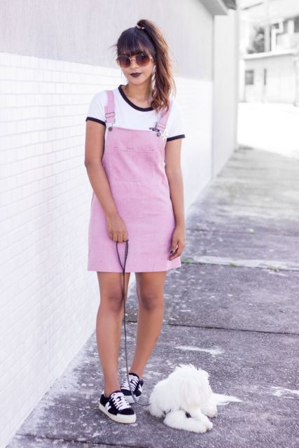Modelo usa salopete rosa claro com blusa branca e preto com tenis no mesmo tom.