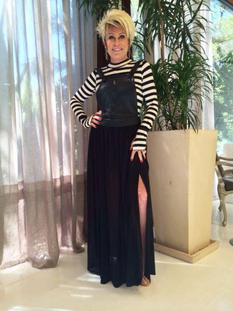Ana Maria Braga veste salopete preta com fenda, blusa listrada em cores preto e branco.