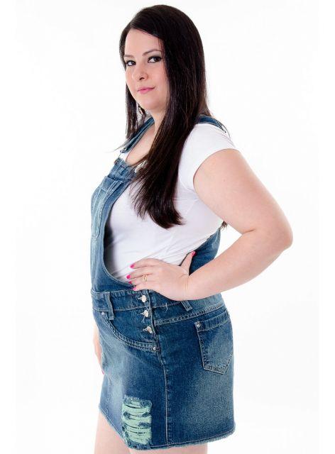 Modelo usa jardineira zaul escuro com detalhes desbotados e blusa branca. manga curta