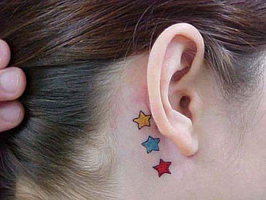 Modelo de tatuagem colorida de estrela, em tom de amarelo, azul e vermelho.