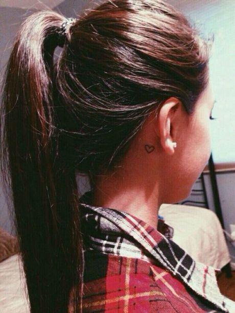 Modelo com tatuagem atras da orelha de coração.