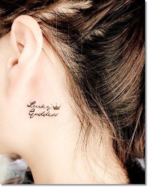 Modelo com tatuagem escrita em ingles, atras da orelha.