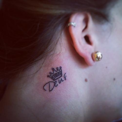 Modelo com tatuagem escrita Deus, atras da orelha.