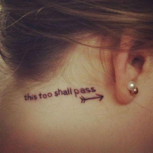 Modelo com tatuagem this too shall pass, atras da orelha.