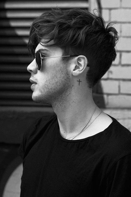 Modelo com tatuagem atrás da orelha.